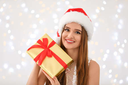Happy young woman in Santa hat with gift box against blurred Christmas lights