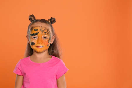 Cute little girl with face painting on orange background. Space for text