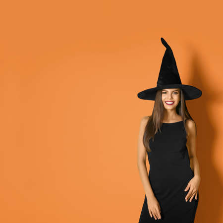 Beautiful woman wearing witch costume for Halloween party on yellow background, space for text