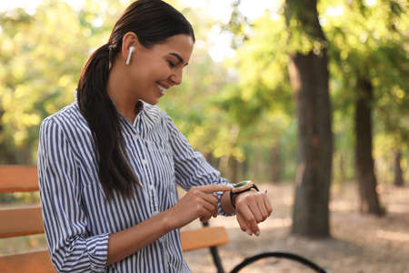 Young woman with wireless earphones and smart watch in park 版權商用圖片