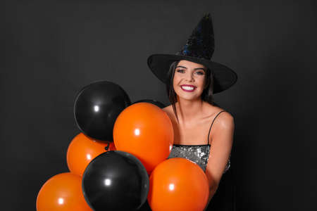 Beautiful woman wearing witch costume with balloons for Halloween party on black background 版權商用圖片