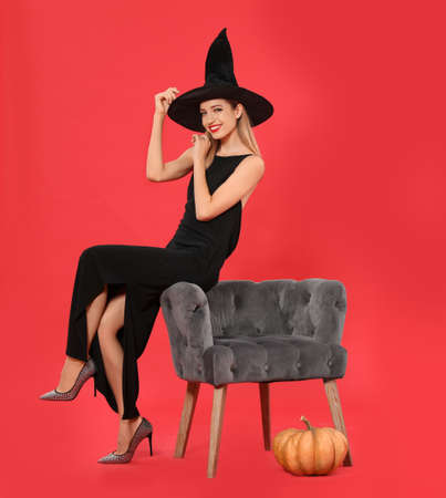 Beautiful woman wearing witch costume near armchair and pumpkin on red background. Halloween party