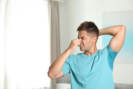 Young man with sweat stain on his clothes indoors, space for text. Using deodorant