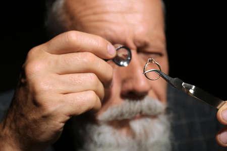 Male jeweler evaluating diamond ring in workshop, closeup view Banco de Imagens