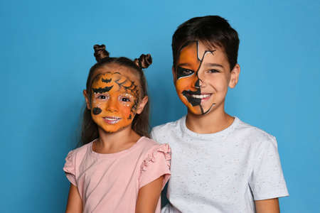 Cute little children with face painting on blue background Stok Fotoğraf