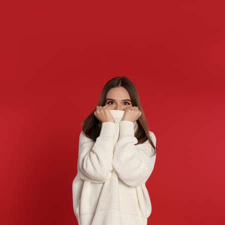 Beautiful young woman in white sweater on red background. Winter season 版權商用圖片