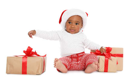 Festively dressed African-American baby with Christmas gifts on white background