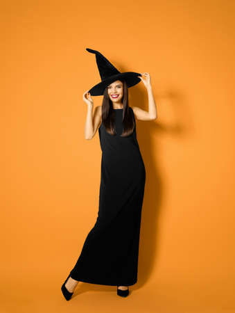 Beautiful woman wearing witch costume for Halloween party on yellow background