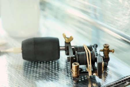 Modern professional tattoo machine on table in salon 写真素材