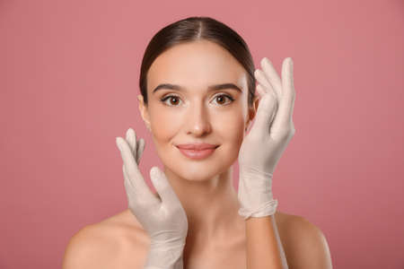 Doctor examining womans face before plastic surgery on pink background 版權商用圖片
