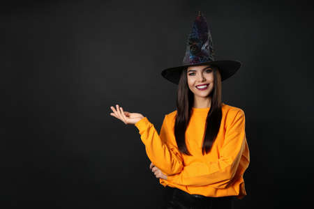 Beautiful woman wearing witch costume for Halloween party on black background, space for text 版權商用圖片