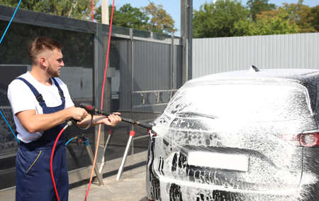 Young worker cleaning automobile with high pressure water jet at car wash
