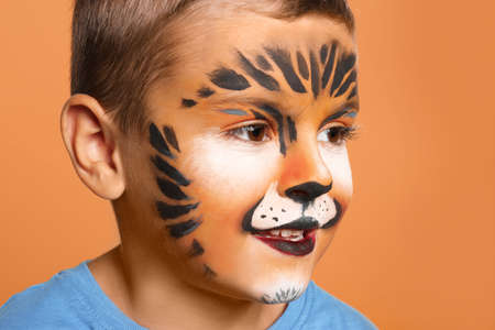 Cute little boy with face painting on orange background