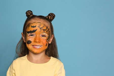 Cute little girl with face painting on blue background. Space for text