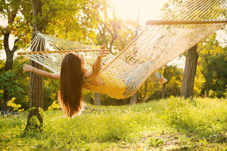 Young woman resting in comfortable hammock at green garden