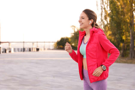 Young woman with wireless headphones listening to music outdoors. Space for text