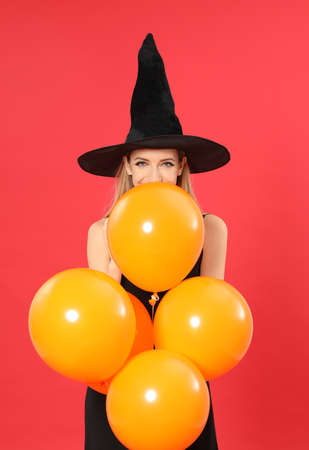 Beautiful woman wearing witch costume with balloons for Halloween party on red background