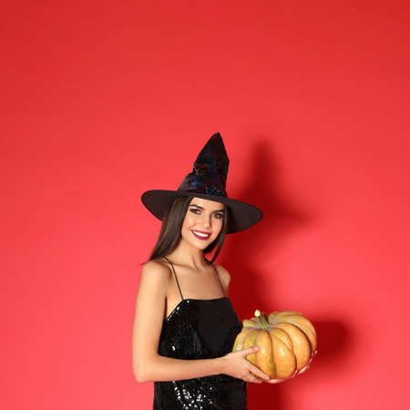 Beautiful young woman wearing witch costume with pumpkin for Halloween party on red background