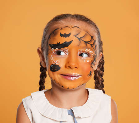 Cute little girl with face painting on orange background 스톡 콘텐츠 - 131666705