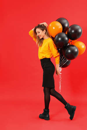 Beautiful woman with balloons on red background. Halloween party 版權商用圖片