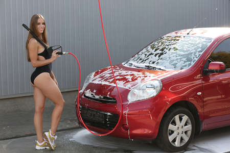 Young woman in swimsuit with high pressure water jet cleaning automobile at car wash 版權商用圖片