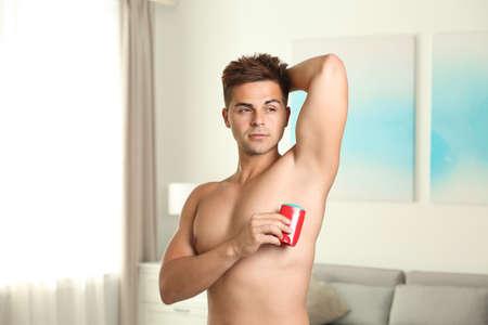 Young man applying fresh deodorant to armpit indoors 写真素材