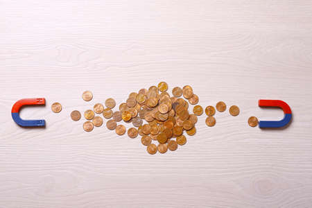 Magnets attracting coins on light wooden background, flat lay 写真素材