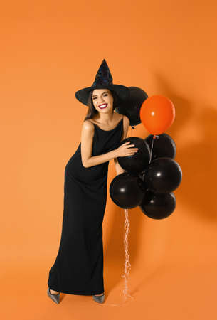 Beautiful woman wearing witch costume with balloons for Halloween party on yellow background 版權商用圖片
