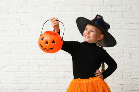 Cute little girl with pumpkin candy bucket wearing Halloween costume near white brick wall