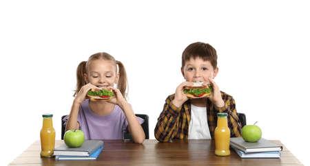 Glückliche Kinder mit gesundem Essen zum Mittagessen in der Schule am Schreibtisch auf weißem Hintergrund