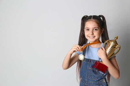 Happy girl with golden winning cup and medal on light background. Space for text