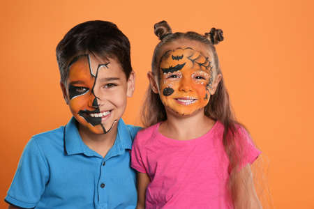 Cute little children with face painting on orange background Stok Fotoğraf