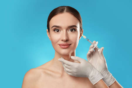 Beautiful woman getting facial injection on light blue background. Cosmetic surgery