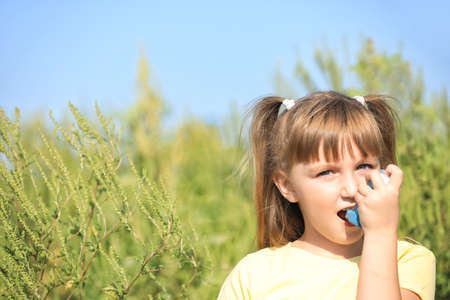 Little girl with inhaler suffering from ragweed allergy outdoors