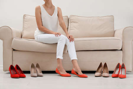 Woman trying on different shoes indoors, closeup