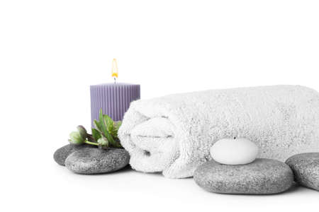 Composition with spa stones, towel and candles isolated on white Фото со стока