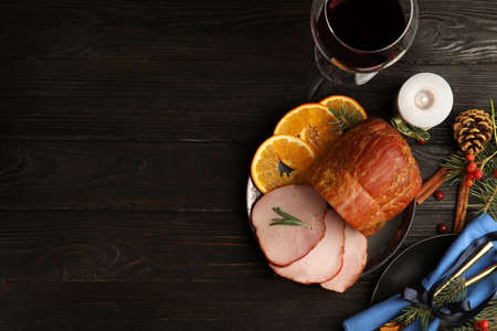 Flat lay composition with delicious ham on black wooden table, space for text. Christmas dinner