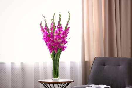 Vase with beautiful pink gladiolus flowers on wooden table in room, space for text Stock fotó - 131456010