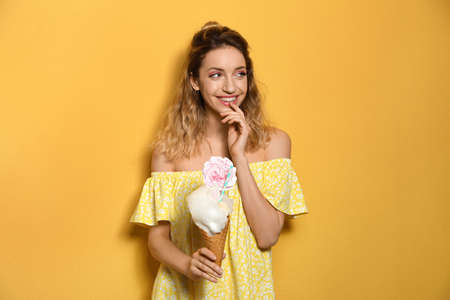 Portrait of young woman holding cotton candy dessert on yellow background
