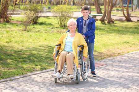 Senior woman in wheelchair with her grandson on sunny day outdoors