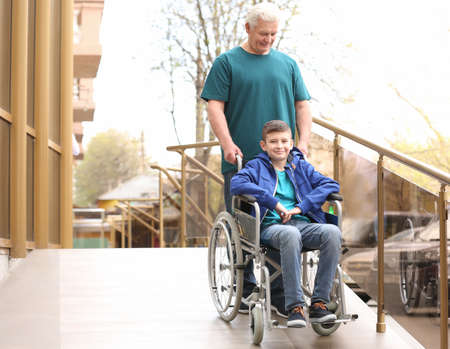 Preteen boy in wheelchair with his grandfather using ramp outdoors