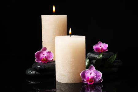 Composition with candles and spa stones on black background Фото со стока