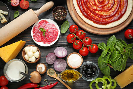 Flat lay composition with pizza crust and ingredients on dark wooden table
