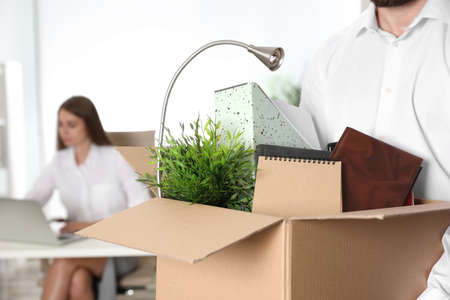 Young man carrying box with stuff in office, closeup