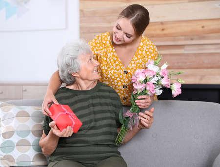 Junge Frau, die ihrer älteren Mutter zu Hause gratuliert. Schönen Muttertag