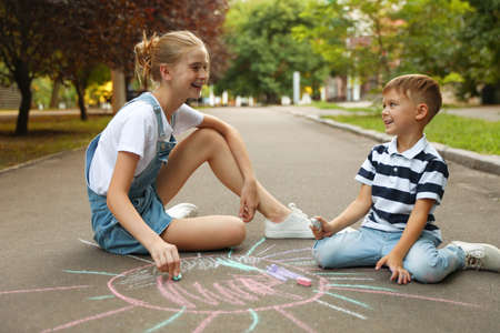Teen nanny and cute little boy drawing sun with chalks on asphalt Imagens
