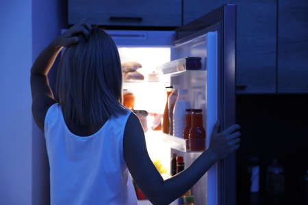 Woman looking into refrigerator full of products at night Zdjęcie Seryjne