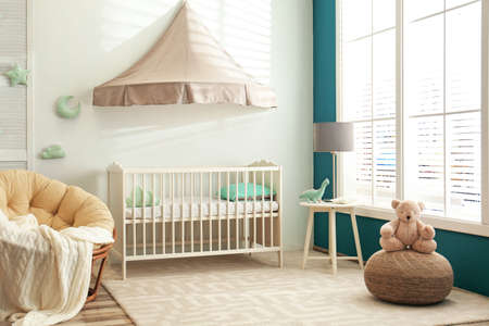 Cute nursery interior with comfortable crib near white wall