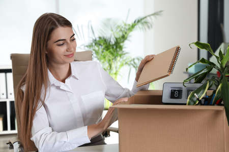Happy young woman packing stuff in box at office Standard-Bild - 132004162
