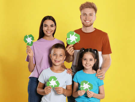 Young family with recycling symbols on yellow background Reklamní fotografie - 132241520